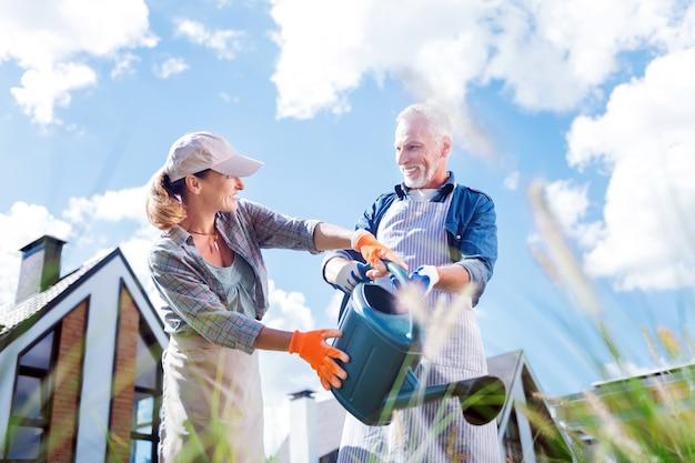 Con mio marito. donna bionda che indossa guanti arancioni luminosi e grembiule beige che innaffia le piante con il marito