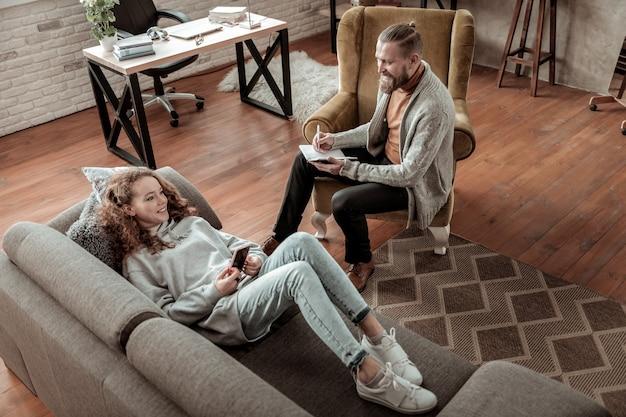 Con psicologo. vista dall'alto di un adolescente che indossa jeans sdraiato sul divano e parla con lo psicologo