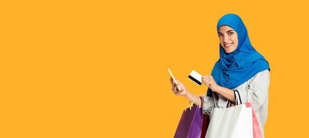 Con smartphone e carta. giovane donna musulmana con pacchetti della spesa in casual su giallo