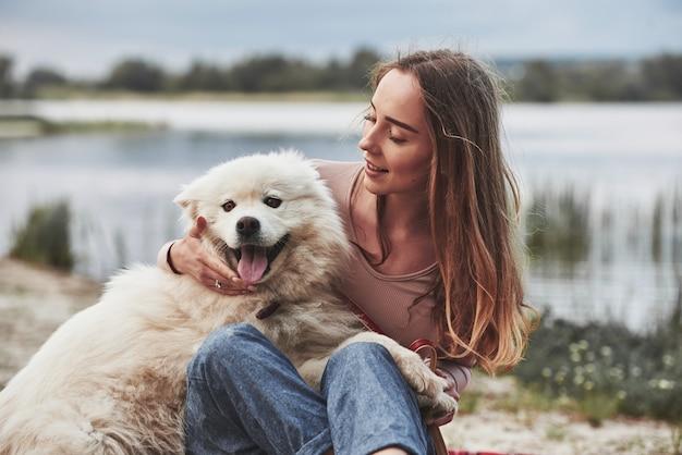 Con la lingua fuori. fa caldo lì. la ragazza bionda con il suo simpatico cane bianco si diverte molto su una spiaggia.