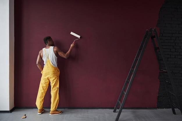 Con la piastra bianca in mano. il giovane operaio afroamericano in uniforme gialla ha qualche lavoro