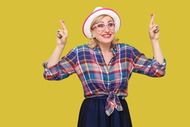 Con per vincere. ritratto di speranza compiaciuta moderna elegante donna matura in stile casual con cappello e occhiali in piedi con dito incrociato e guardando. studio al coperto colpo isolato su sfondo giallo.