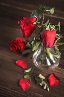 Rosa appassita su sfondo grigio scuro e tavolo in legno con petali e foglie autunnali, concetto di design del triste romanticismo di san valentino, rotto, copia, spazio.
