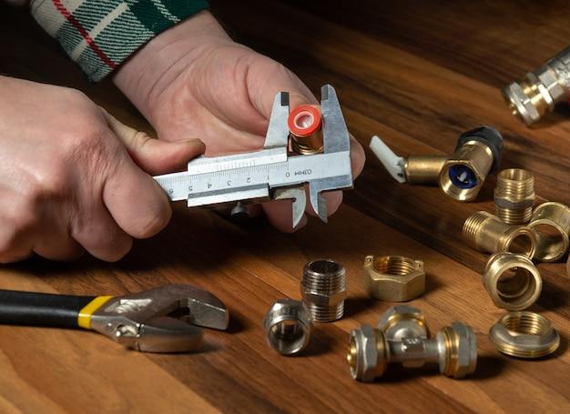 La procedura guidata misura la dimensione del raccordo utilizzando una pinza prima di collegare il tubo dell'acqua o del gas. primo piano delle mani del maestro