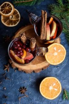Wo bicchieri di vin brulé rosso caldo decorato con arancia