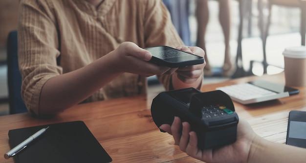 Una donna che usa il suo cellulare per effettuare un pagamento senza fili con una macchina edc o un terminale per carte di credito. concetto di pagamento mobile con carta di credito virtuale