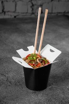Wok in scatola tagliatelle piccanti in contenitore per alimenti nero