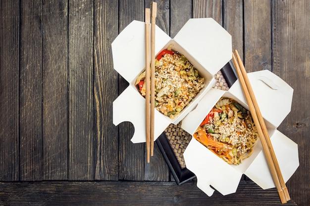Tagliatelle al wok udon e riso con frutti di mare e pollo in scatola su nero