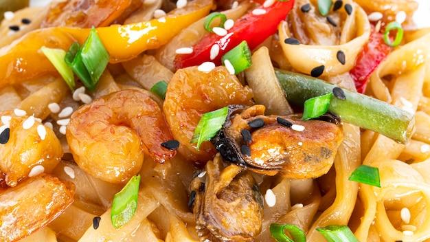 Tagliatelle al wok con frutti di mare. pasta con gamberi e cozze