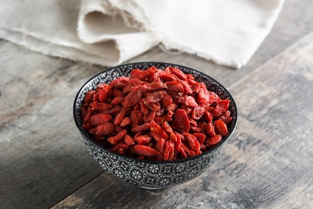 Wolfberries o bacche di goji in ciotola sulla tavola di legno