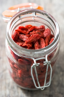 Bacche di wolfberries o goji in barattolo sulla tavola di legno