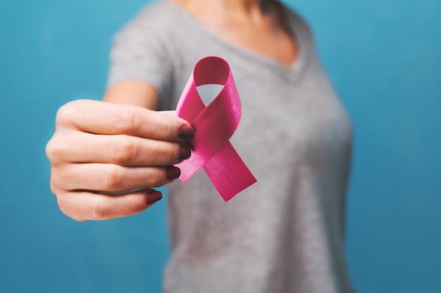 Mano della donna che tiene la consapevolezza del cancro al seno del nastro rosa concetto di sanità e medicina