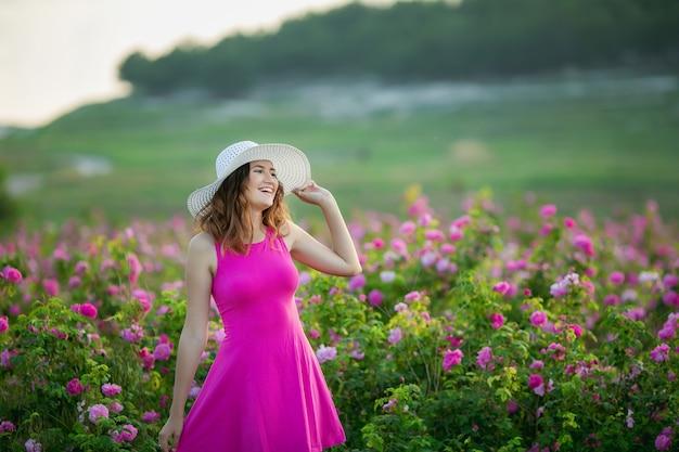 Una donna di 25-30 anni di buon umore cammina su un campo naturale naturale con fiori