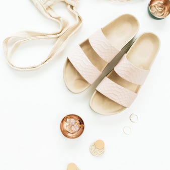 Accessori donna: ciabatte, borsa con lacci, orecchini e anelli su superficie bianca