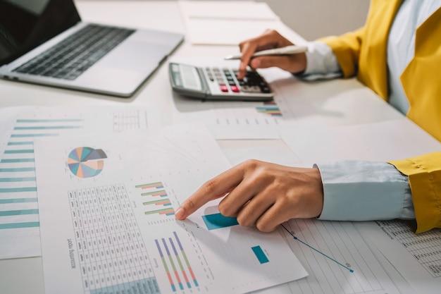 Il ragioniere della donna usa la calcolatrice e il computer con la penna sulla scrivania in ufficio. concetto di finanza e contabilità