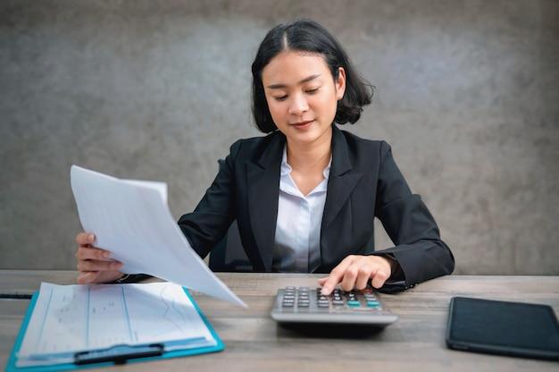 Ragioniere della donna utilizzando la calcolatrice per calcolare il rapporto finanziario in ufficio