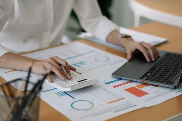 Ragioniere donna che utilizza calcolatrice e computer portatile per budget finanziario e carta di prestito in ufficio.