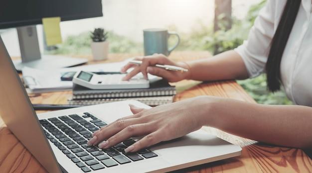 Ragioniere donna che lavora con computer e calcolatrice per spese aziendali e finanziarie