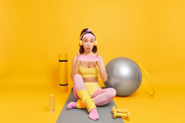 La donna in activewear allunga le braccia con la fascia di resistenza pone sul tappetino fitness fa esercizi per perdere peso aumentare la flessibilità sembra scioccata