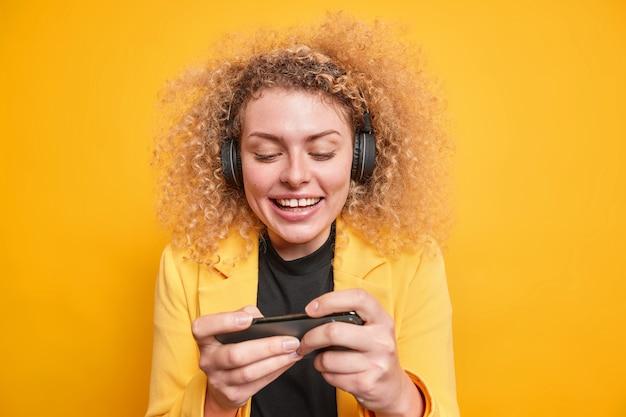 Donna dipendente dalle moderne tecnologie gioca con i videogiochi tiene lo smartphone orizzontalmente indossa le cuffie wireless vestita con una giacca