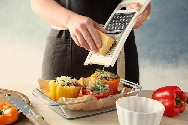 Donna che aggiunge formaggio alla quinoa peperoni ripieni in cucina
