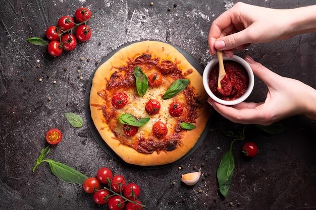 Donna che aggiunge salsa di pomodoro alla pizza appena sfornata