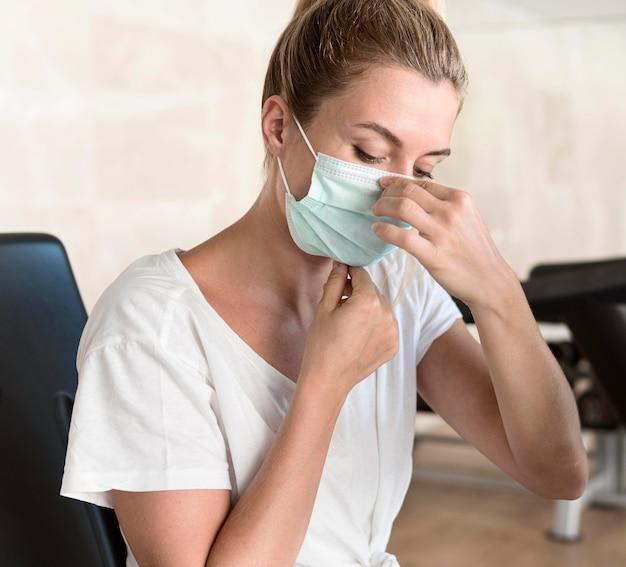 Donna che adegua la sua maschera medica in palestra