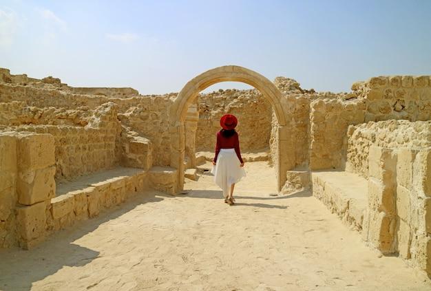 Donna che ammira il forte del bahrain o qal'at al-bahrain a manama, bahrain