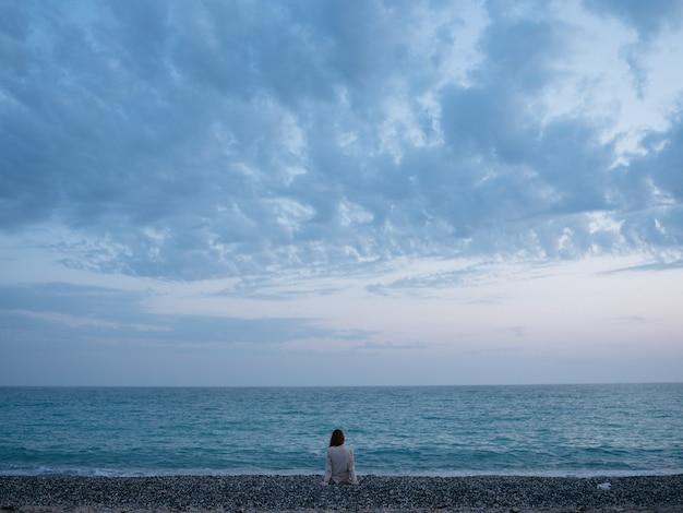 Donna che ammira la natura di sera di rilassamento del paesaggio dell'oceano
