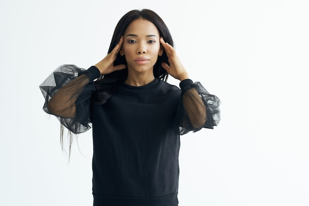 Posa dello studio del modello della giacca scura di aspetto africano della donna