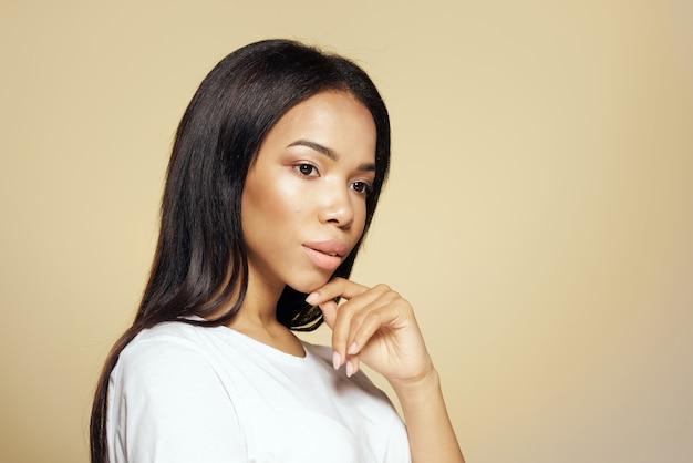 Donna di aspetto africano capelli lunghi scuri maglietta bianca sfondo beige