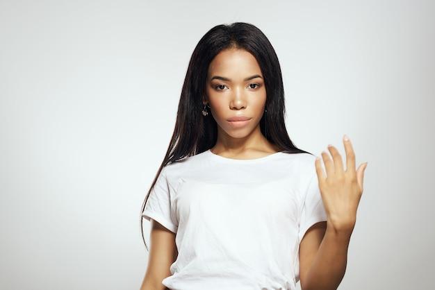 Donna dall'aspetto africano con i capelli lunghi nei cosmetici della maglietta bianca