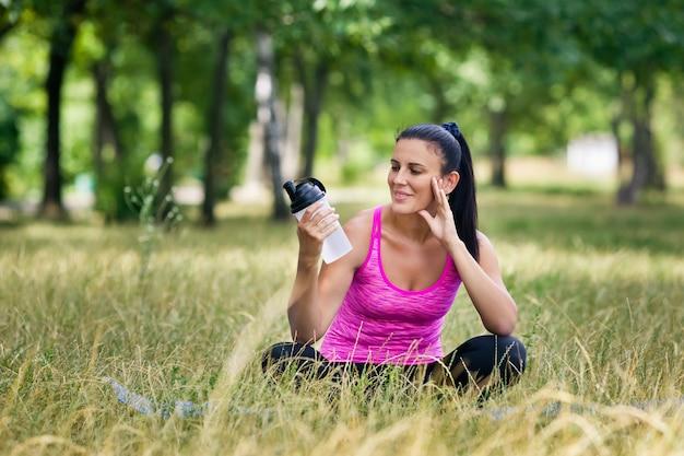 Donna dopo lo yoga con una bottiglia d'acqua si siede sull'erba