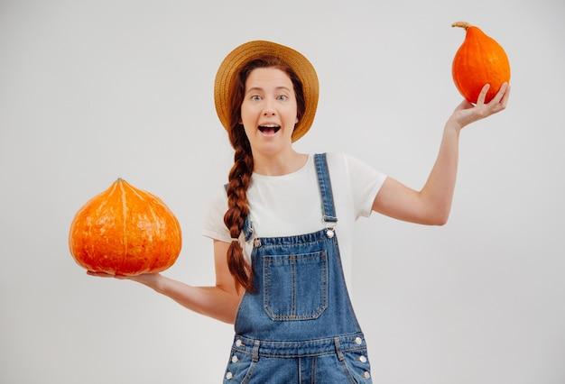 La donna dell'agricoltura pesa una zucca organica grande e piccola con il suo concetto di raccolta delle mani