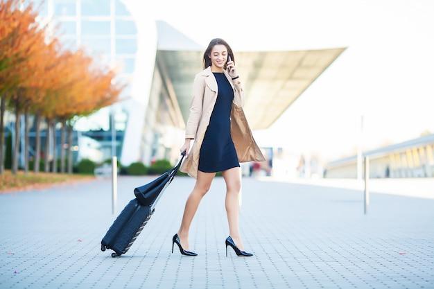 Donna in aeroporto a parlare sullo smartphone mentre si cammina con il bagaglio a mano in aeroporto andando a gate