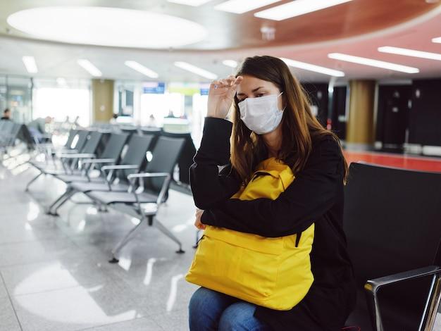 Donna all'aeroporto con maschera medica in attesa dello zaino giallo del passeggero. foto di alta qualità
