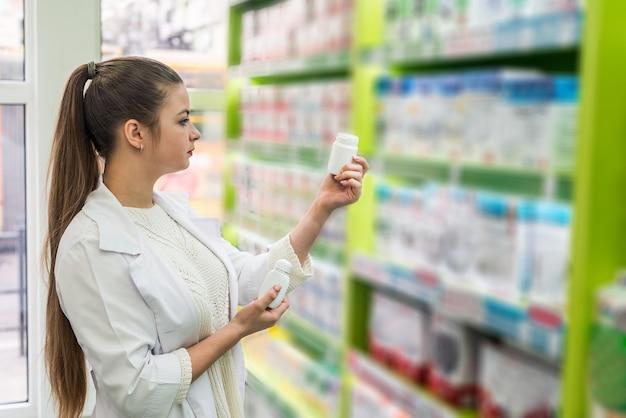 Speziale donna guardando il contenitore con compresse in farmacia