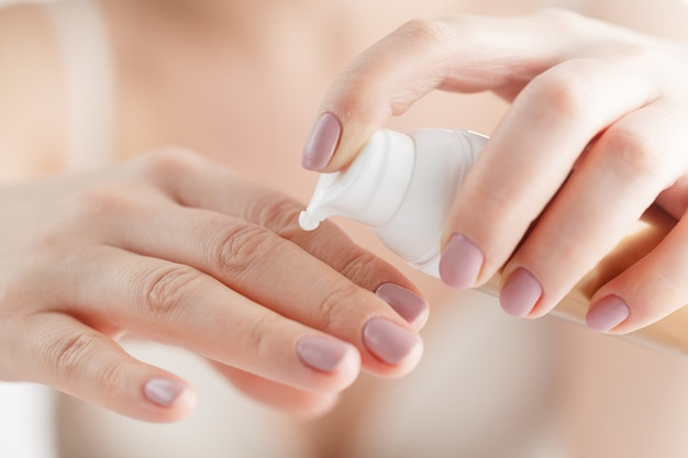 La donna applica la crema sulle mani dopo il bagno. concentrarsi sulle mani