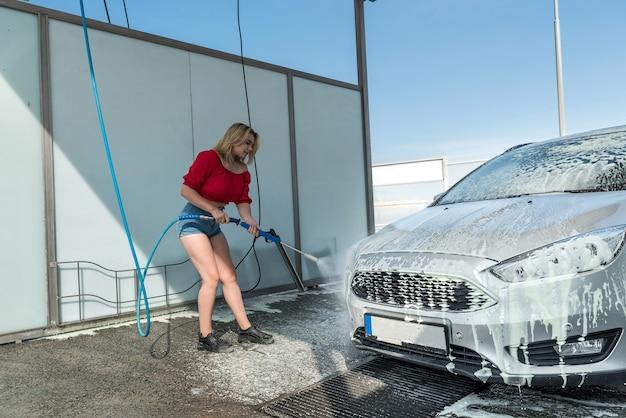 La donna applica la schiuma all'automobile con il tubo flessibile. stile di vita pulito