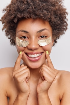 La donna applica cerotti dorati sotto gli occhi per ridurre le rughe sorrisi mostra ampiamente denti bianchi sta a torso nudo gode di procedure di bellezza pose indoor