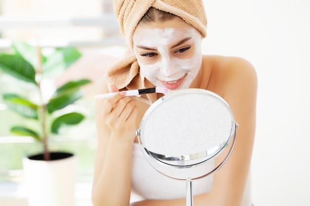 La donna applica la maschera all'argilla bianca per la cura della pelle del viso nel bagno di lusso dell'hotel