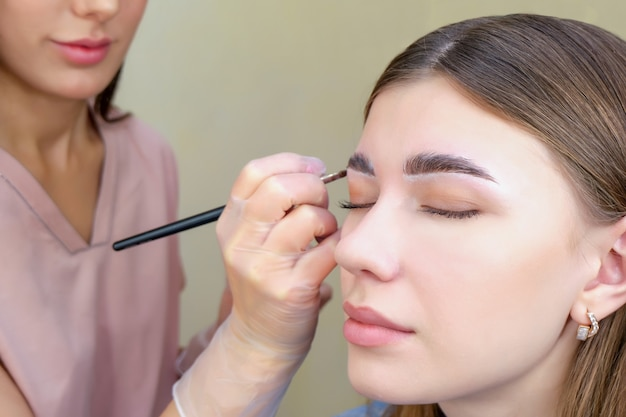 Donna che applica la tinta della fronte con il primo piano della spazzola di trucco