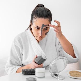Donna che applica la maschera per il viso all'argilla