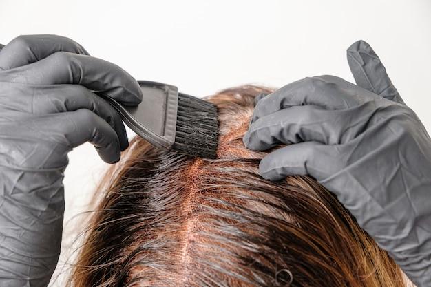 Donna che applica una tinta di colore ai capelli castani usando un pennello. tintura delle radici grigie dei capelli a casa.