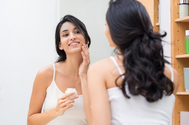 Donna che applica la crema sul viso