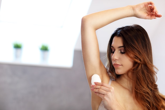 Donna che applica deodorante sull'ascella in bagno