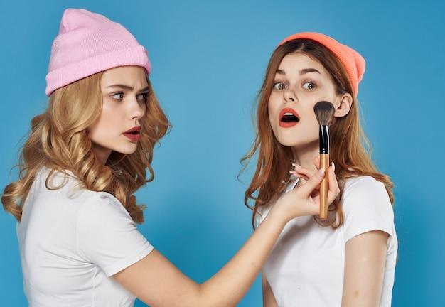Donna che applica il trucco al suo stile di vita dei cosmetici dell'amicizia del viso dell'amica