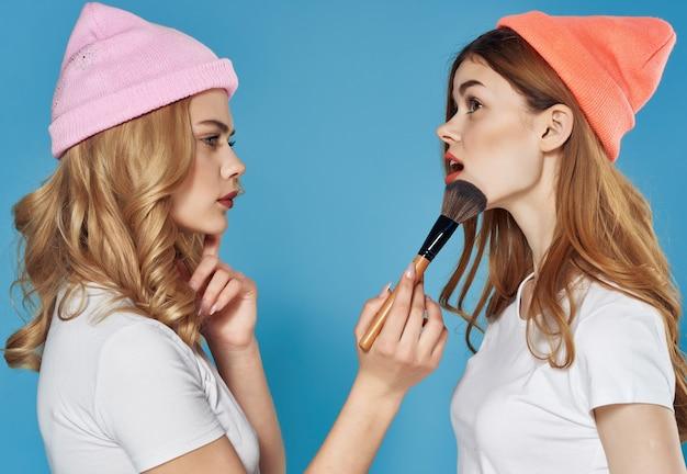Donna che applica il trucco alla sua amica amicizia premurosa sfondo blu