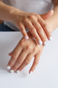 Donna che applica crema idratante alle sue mani