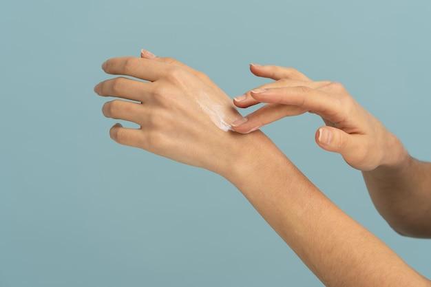 Donna che applica crema protettiva sulla pelle secca delle mani nella stagione fredda o nel periodo di riscaldamento in inverno a casa